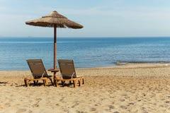 Umbrella and sun loungers on the empty beach stock photo