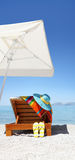 Umbrella and sunbed on the beach with blue hat, flip flop Royalty Free Stock Photos