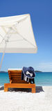 Umbrella and sunbed on the beach with hat, and towel Royalty Free Stock Photos