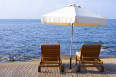 Umbrella and sunbeds against sea Stock Photography