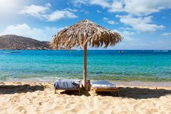 The famous Mylopotas beach on the island of Ios, Cyclades, Greece. Umbrella and sunbeds in front of turqouise sea at the famous Mylopotas beach on the island of stock photos