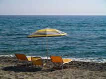 Umbrella and three sunbeds on the beach Stock Photography