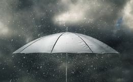 Umbrella in thunderstorm. Umbrella under raindrops of thunderstorm Royalty Free Stock Image