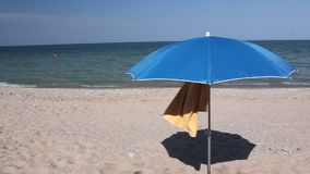 Umbrella and towel at the beach. In the breeze stock video footage