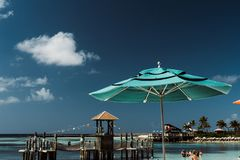 Umbrella in tropical location. A blue or teal green umbrella in a tropical location in the Bahamas or Caribbean island or some tropic island a place to relax or royalty free stock photo