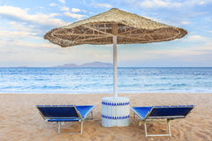 Umbrella and two empty deckchairs on the shore sand beach Royalty Free Stock Image