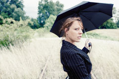Umbrella woman. A young woman has a umbrella in her hand and looking intensive into the camera Royalty Free Stock Photography