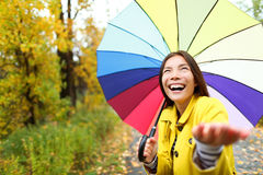 Umbrella woman in Autumn excited under rain. On fall day.Beautiful young female wearing raincoat surprised and excited in the rain. Mixed race Asian Caucasian Royalty Free Stock Photography