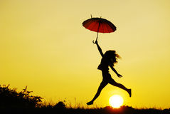 Umbrella woman jump and sunset Royalty Free Stock Photography