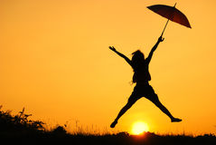 Umbrella woman jump and sunset Stock Photo