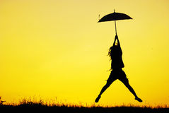 Umbrella woman jump and sunset silhouette Stock Photo
