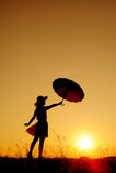 Umbrella woman jump and sunset silhouette Stock Photos