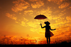 Umbrella woman jump and sunset silhouette Stock Images