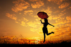 Umbrella woman jump and sunset silhouette Royalty Free Stock Image