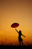 Umbrella woman jump and sunset silhouette Royalty Free Stock Photography