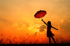 Umbrella woman jump and sunset silhouette Royalty Free Stock Photos