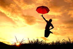 Umbrella woman jump and sunset silhouette in Lake. Umbrella woman jumping and sunset silhouette in Lake Stock Photo