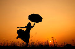 Umbrella woman jumping and sunset silhouette Royalty Free Stock Photography