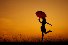 Umbrella woman jumping and sunset silhouette when she happy Stock Images