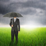 Umbrella woman standing to raincloud in grassland with umbrella Stock Images