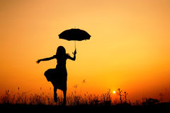 Umbrella woman and sunset silhouette Royalty Free Stock Images