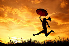 Umbrella woman and sunset silhouette Stock Image