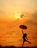 Umbrella woman and sunset silhouette,Water reflect Royalty Free Stock Photo