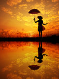 Umbrella woman and sunset silhouette,Water reflection Royalty Free Stock Image
