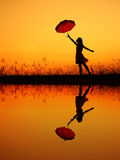 Umbrella woman and sunset silhouette,Water reflection Royalty Free Stock Images