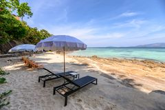 Umbrella with wooden sunbed on the white beach at tropical sea stock photo