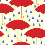 Umbrellas. Seamless from drops and umbrellas on yellow background Stock Photos