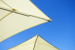 Umbrellas. The edges of two white umbrellas in front of blue sky sunny background Royalty Free Stock Photography