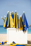 Umbrellas. White container with blue and yellow parasol on beach Royalty Free Stock Photo