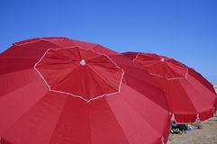 Umbrellas. Red umbrellas provide shade for the parents at a youth soccer game Royalty Free Stock Image