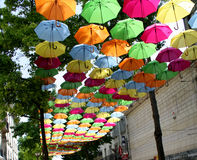 Umbrellas in the air down a street in France. Multi colored ( coloured ) umbrellas in the air down a street in France royalty free stock images