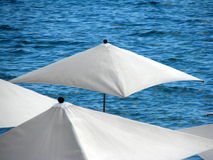 Umbrellas on the beach. A detail of some white umbrellas on the seaside Royalty Free Stock Photos