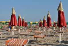 Umbrellas on the beach. With deck chairs for sun protection and overlooking the Adriatic sea in Italy stock photos