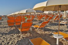 Umbrellas on the beach. With deck chairs for sun protection and overlooking the Adriatic sea in Italy stock image