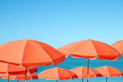 Umbrellas on the beach. Orange beach umbrellas against a blue background of the sea and sky Stock Photos