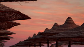 Umbrellas on the beach against the sky at sunset stock video footage