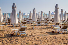 Umbrellas and beach chairs on empty the beach. Royalty Free Stock Photos