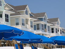 Umbrellas and Beach Houses. Row of beach houses above blue umbrellas