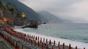 Umbrellas at the beach in Monterosso al Mare. Cinque Terre, Italy, rainy day, sea with waves and mountains in fog at horizon, evening lights stock video