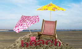 Umbrellas and beach text in the sand. Beach setting with chair umbrella and text Royalty Free Stock Image