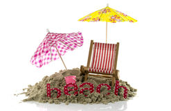 Umbrellas and beach text in the sand. Beach setting with chair umbrella and text Royalty Free Stock Photography