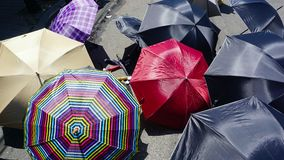 Umbrellas. Big group of umbrellas laying in the floor, different kinds of umbrellas resting over the street in a sunny day Royalty Free Stock Images