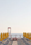 Umbrellas and chairs on a bathing establishment. Some umbrellas and chairs in an empty bathing establishment, with rescue tower and boat, at the beach of Royalty Free Stock Images