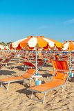 Umbrellas and chaise lounges on the beach of Rimini in Italy.  stock images