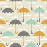 Umbrellas in the clouds. Seamless texture. Autumn. Depicts the umbrellas of the same size .Umbrella in three colors : grey, yellow and blue .Umbrellas in the Stock Photo