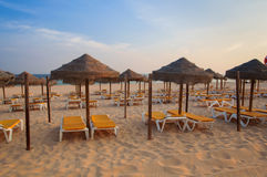 Umbrellas and deck lounges in the beach at sunset. Algarve, Portugal Stock Photography